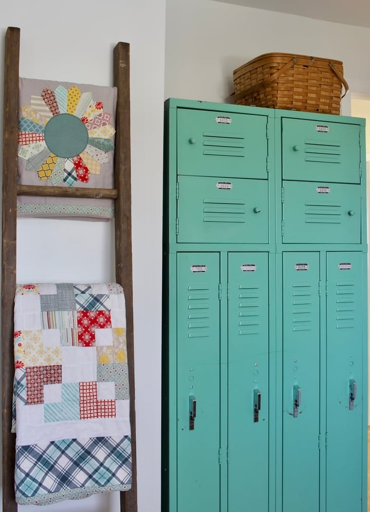Quilts on a vintage ladder and vintage lockers
