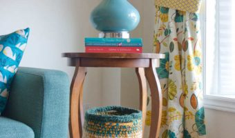 Two crocheted baskets by a side table in living room