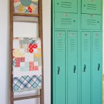 Vintage aqua lockers beside quilts on a ladder