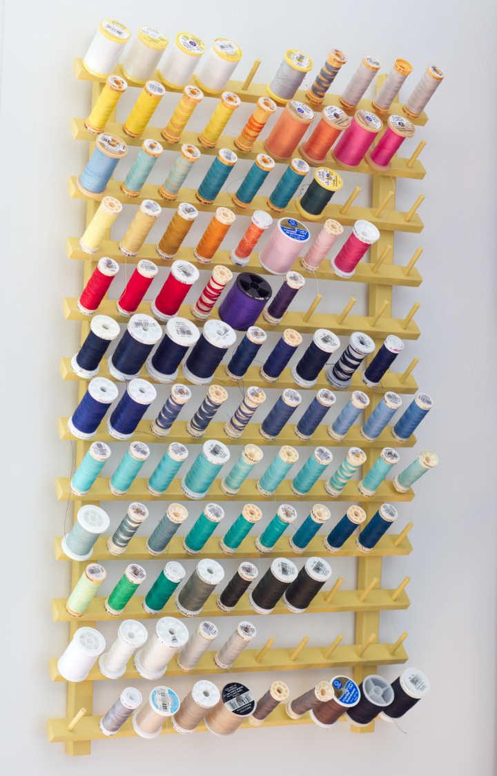 Yellow painted thread rack full of a rainbow of thread