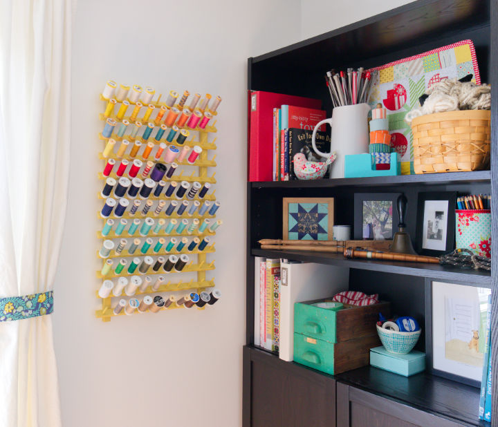 After shot of yellow thread rack and colourful rainbow of thread hanging on wall by bookshelf
