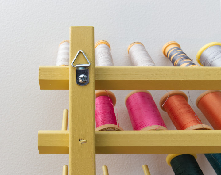 Back of the thread rack showing a triangular hanger that hooks over a screw