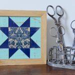 Vintage scissors beside a painted wooden quilt block