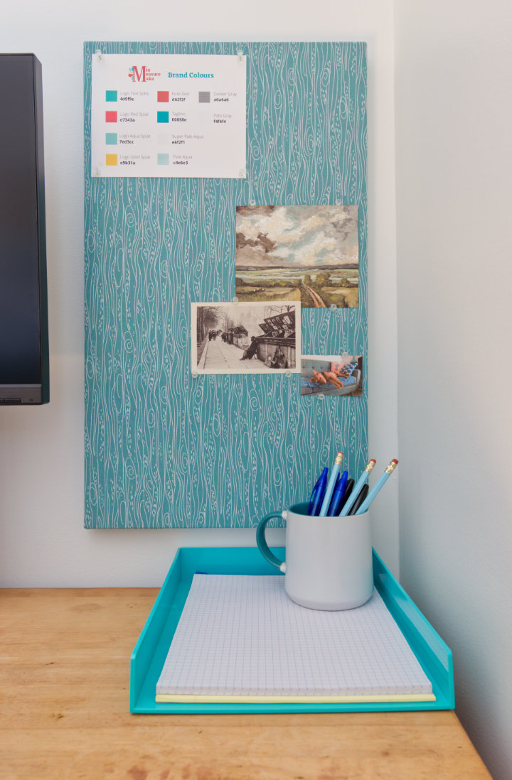 After shot of aqua fabric covered cork board with art on it