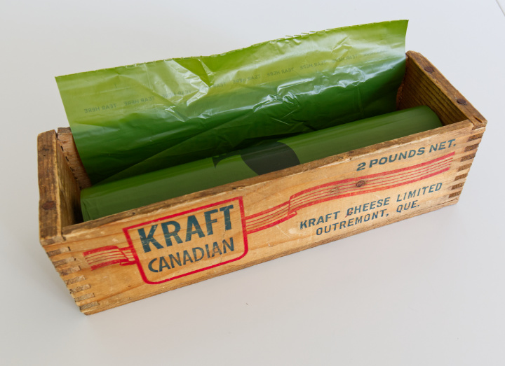 A roll of dog waste bags fits perfectly inside an old wood Kraft Cheese box
