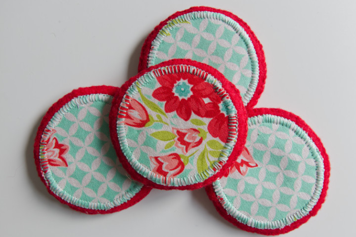 Close up of red and aqua pattern weights stitched with a blanket stitch