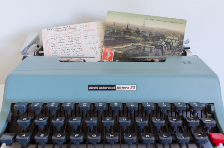 Green vintage typewriter with vintage postcards - contact us