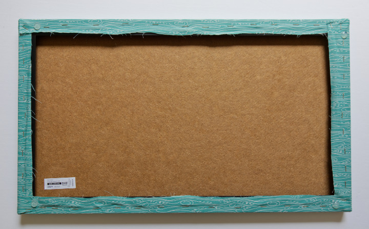 Back of the fabric covered cork board with all staples and adhesive bumper dots in the corners