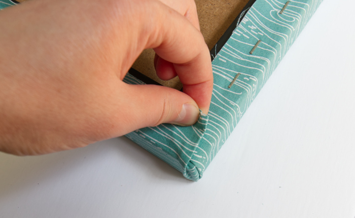 Fingers folding the left flap over so that the fold is parallel with the corner