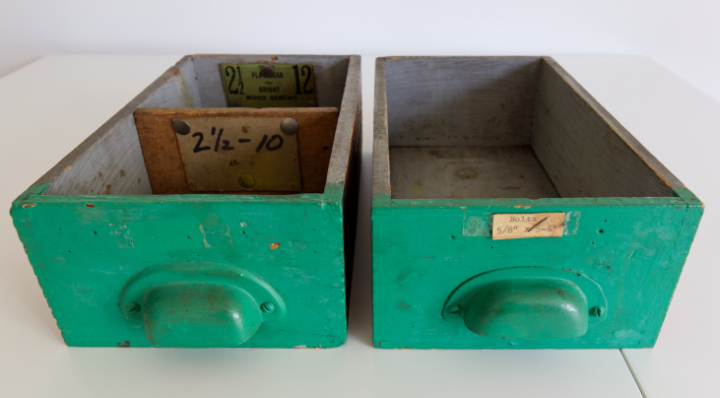 Two vintage green drawers with pull handles, and vintage hardware tags on them