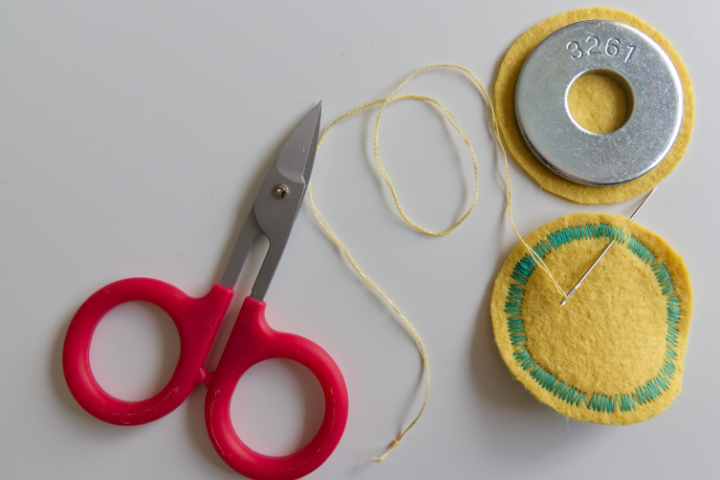 Needle coming from back of top circle with floss, coming out near edge to begin stitching