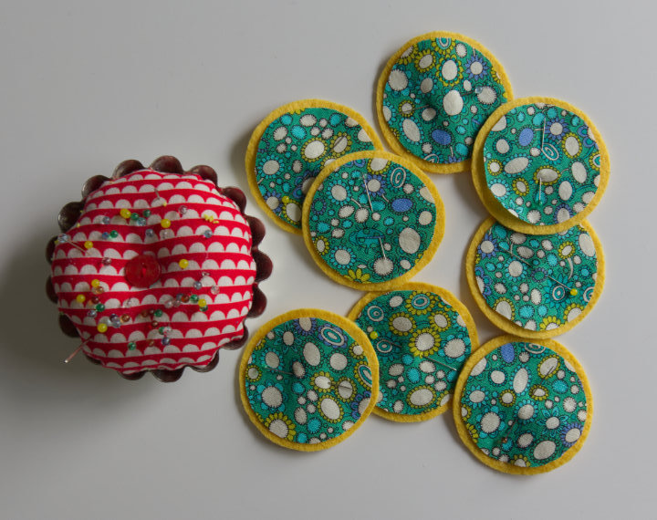 Fabric circles have been pinned to felt circle tops, sitting beside pin cushion