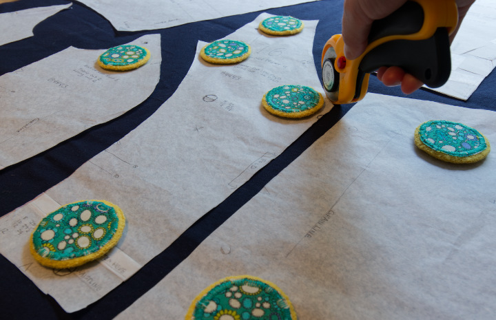 Sewing patterns laid out on fabric with pattern weights while rotary cutter cuts around them