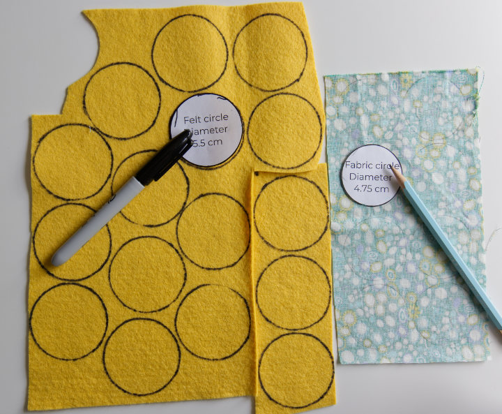 16 circles have been traced onto felt with a sharpie and 8 circles traced onto fabric with pencil