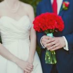 Red and aqua wedding colours couple posing with red carnation bouquet and aqua ribbon