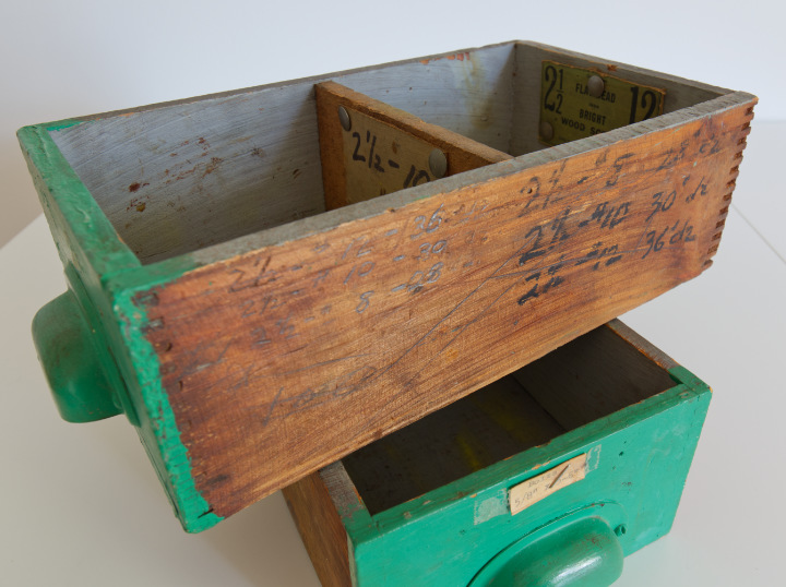 Two vintage wood drawers painted bright green, stacked, one has hardware measurements written on the side