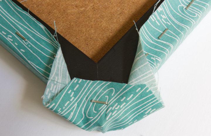 Fold the corner down and put one staple, making two flaps of fabric on either side