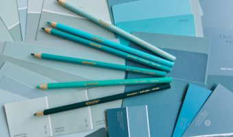 A pile of teal, turquoise and aqua paint chips and pencil crayons