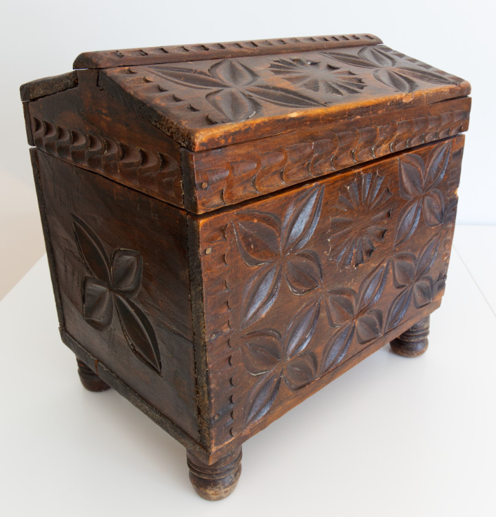 A vintage wood chest with raised feet, dark brown and carved with floral designs