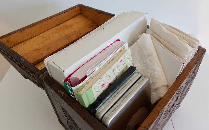 Wedding memorabilia inside old wooden chest - notebooks, dvds, wedding cards, papers