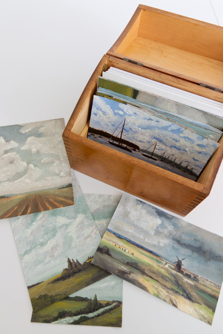 Small index card sized paintings inside old wood recipe box, paintings laid out beside it too