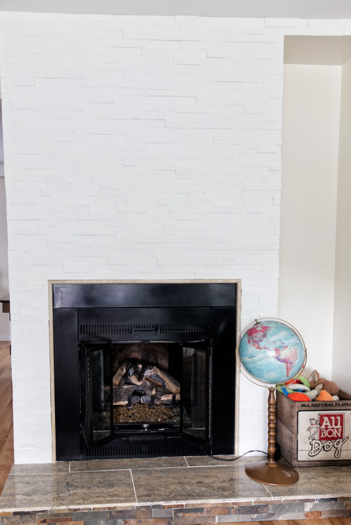 A Painted white stacked stone fireplace with gas insert and a globe and vintage crate of dog toys beside it