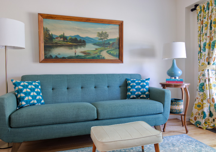 Living room with different styles, new, vintage-style couch, vintage footstool, antique painting and side table, new lamps, 70s-esque curtains