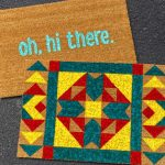 """Two finished painted doormats laying on a driveway, one says """"Oh, hi there"""" and the other is a bright quilt block pattern"""