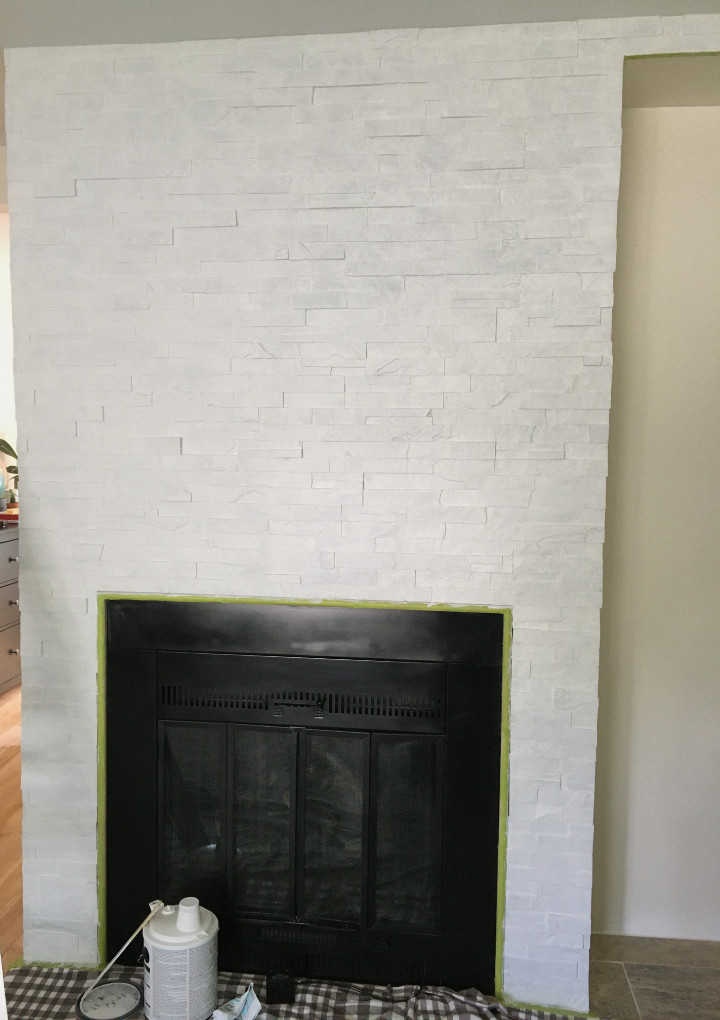 A fireplace with stacked stone that has 3 coats of primer on it.