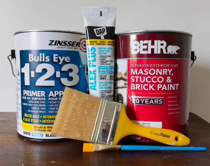 A can of Bullseye 1-2-3 primer beside Behr masonry and stucco paint, caulking, and two paintbrushes