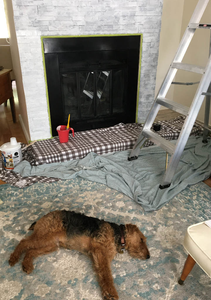 Oliver the dog lays on the floor nearby as Danielle primes the fireplace stone