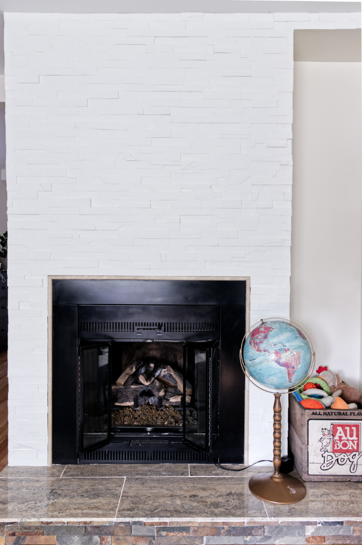 Transformation of fireplace to painted white stacked stone with a globe and vintage crate of dog toys beside