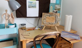 Typical painting set-up on small desk with pullout surface. Bentwood chair. Small easel, monitor covered to protect it and inspiration picture taped up.