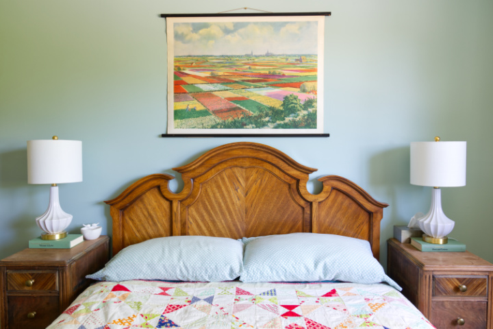 Curved antique headboard in oak with angled wood grain, colourful quilt on the bed, colourful pull down chart of flower fields above the bed, white lamps, blue-green walls.