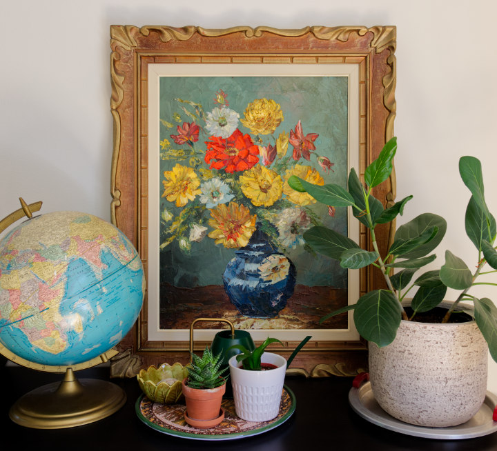 Reasons to buy vintage decor: Creating memories, such as our trip to buy this painting. Large floral oil painting in a gold frame, a globe, and potted plants