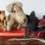 Three vintage toy terriers propped on a book - one Airedale, on Scottie dog on wheels, and one unidentified