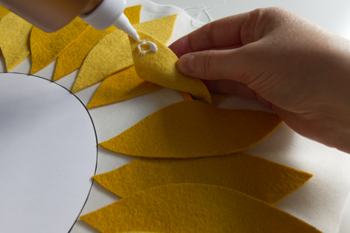 Tacky glue is being applied to the inner tip of a felt petal as it is lifted back