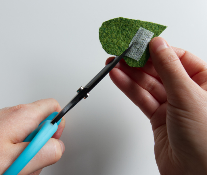 A hand holding aqua Perfect Scissors cutting out tiny leaf shapes of stabilizer on green felt