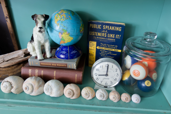 Close-up of books stacked, a ceramic dog, a metal globe, a clock, a row of shells and a glass canister of billiard balls in a vintage metal barrister bookcase