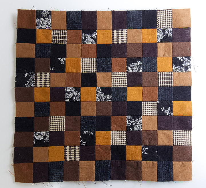 All the black and brown quilting cotton squares have been sewn into a 11x11 grid to make the centre of the DIY fall sunflower