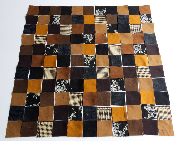 The black and brown quilting cotton squares are laid out in a random and evenly dispersed 11x11 square