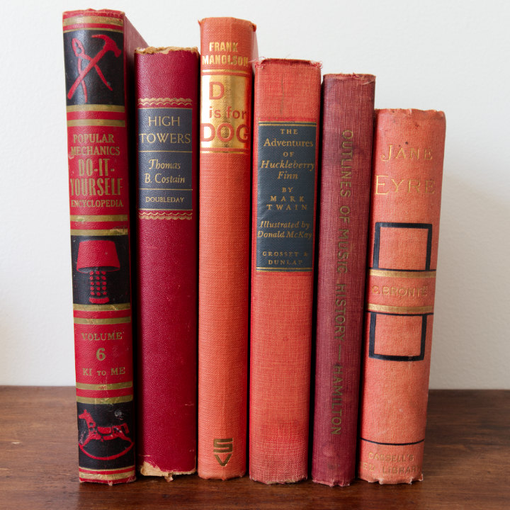 Vintage books as decor for charm -Six red books standing in a row all with black and gold writing on their spines