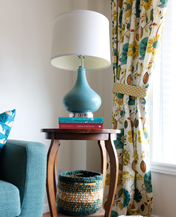Three books prop up a turquoise lamp on a vintage wood side table with a crocheted basket beneath and colorful floral curtains