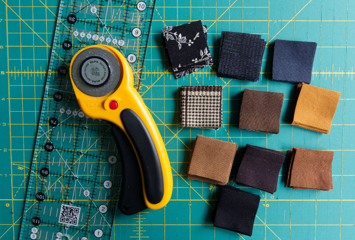 A cutting mat with 1.5 inch squares of black and brown quilting cotton with rotary cutter and quilting ruler