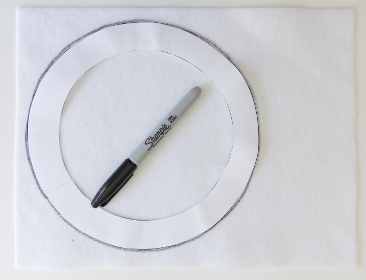 A piece of white acrylic felt with the larger circle template on that has been traced with a Sharpie.