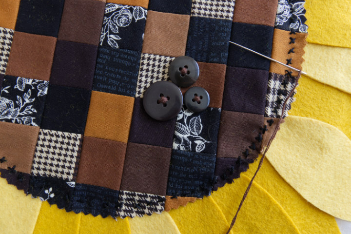 A close-up of the stitching around the outside of the sunflower centre, in little black 'x's in black floss. Buttons have been sewn in a cross.