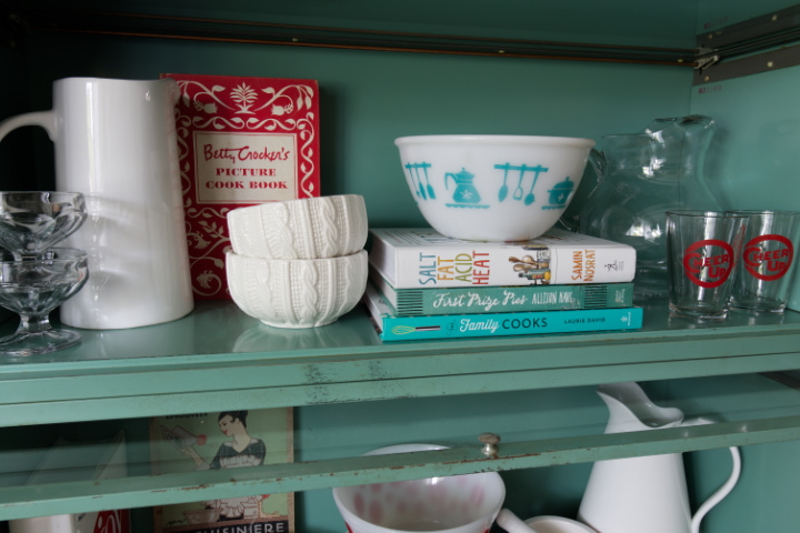 Close up of top shelf with cookbooks, pyrex bowl, Betty Crocker cookbook and white dishes