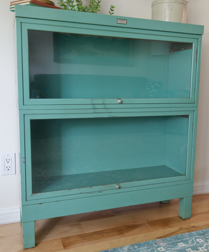 Vintage metal barrister bookcase in blue-green, sitting empty