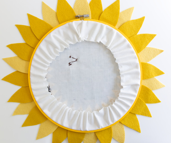 The white fabric in the hoop has been gathered in a circle, as viewed from the back