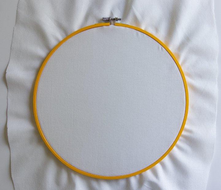 A piece of white fabric has been stretched in a yellow embroidery hoop with extra fabric sticking out to make the base for the DIY fall sunflower